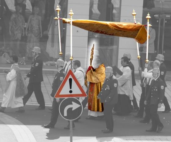 Fronleichnam: Monstranz unter Baldachin mit Achtung-Verkehrsschild