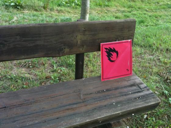 Holzbank, auf der ein rotes Warnschild mit Flamme liegt