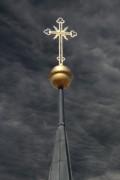 Kirchturmspitze vor dunklen Wolken (Montage)