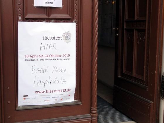 Plakat mit hinzugefügtem handschriftlichem Text: HIER - Erzähl Deine Hauptplatz