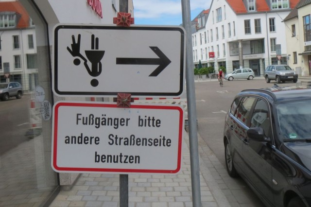 Schild: Fußgänger bitte andere Straßenseite benutzen; Zusatzschild mit Fußgänger-Symbol und Pfeil steht auf dem Kopf