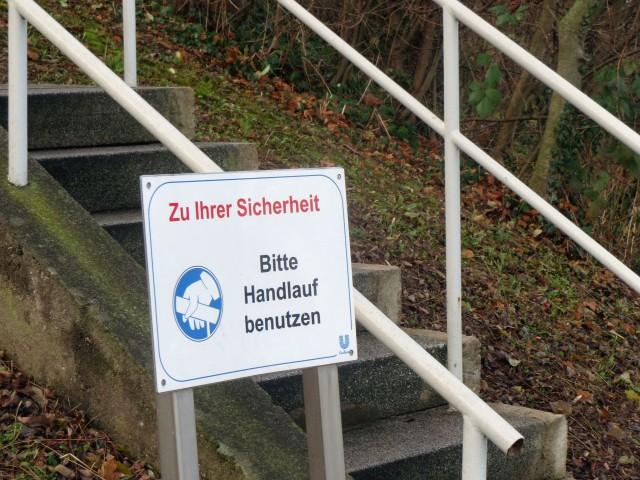 Schild an kleiner Treppe: Zur Ihrer Sicherheit bitte Handlauf benutzen