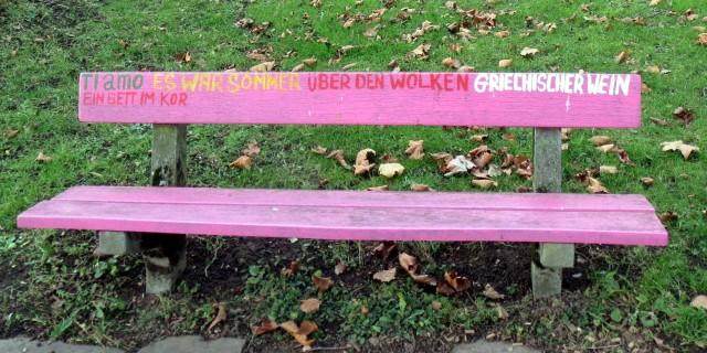 rosa Parkbank, beschriftet mit: Ti amo, Es war Sommer, Über den Wolken, Griechischer Wein, Ein Bett im Kor