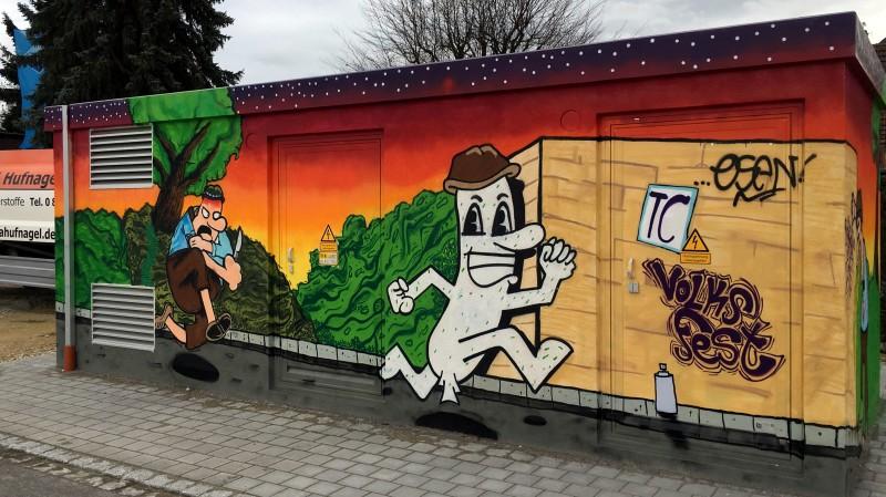 Graffiti: rennende Weißwurst, verfolgt von Mann mit Messer