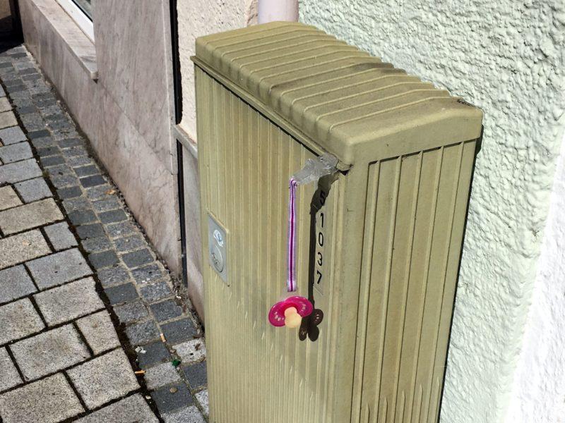 Schnuller, der mit Band mit Klammer an Stromkasten gesteckt ist