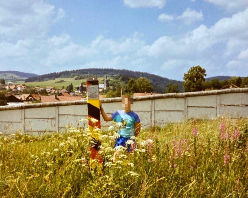 Schwarz-rot-goldener Grenzpfosten (mit Schüler daneben) vor Grenzmauer