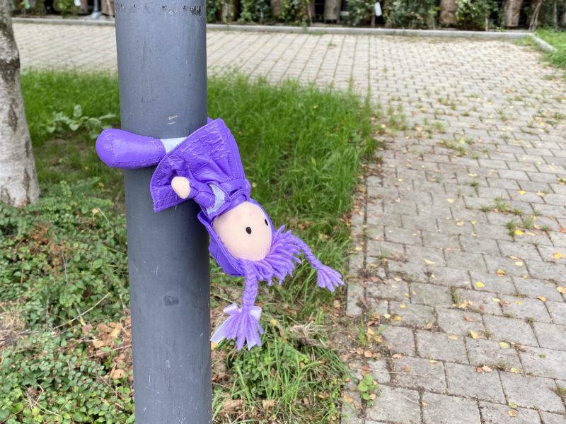 Kleine, violett gekleidete Stoffpuppe hängt fast kopfüber an einem Laternenmast